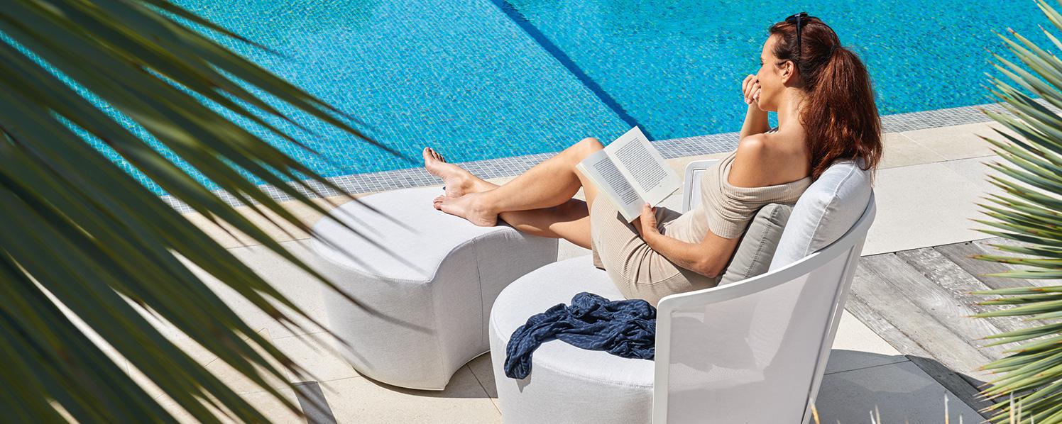 lesende Frau auf Gartensessel mit Hocker
